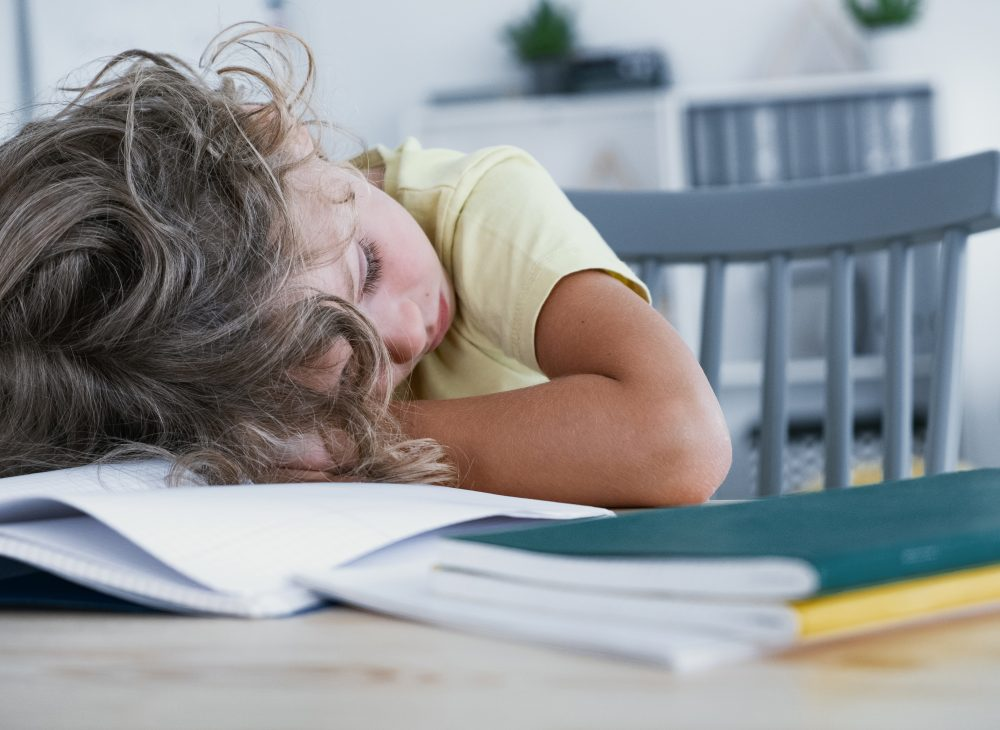 close-up-of-a-tired-kid-sleeping-with-his-head-VE6TYD7