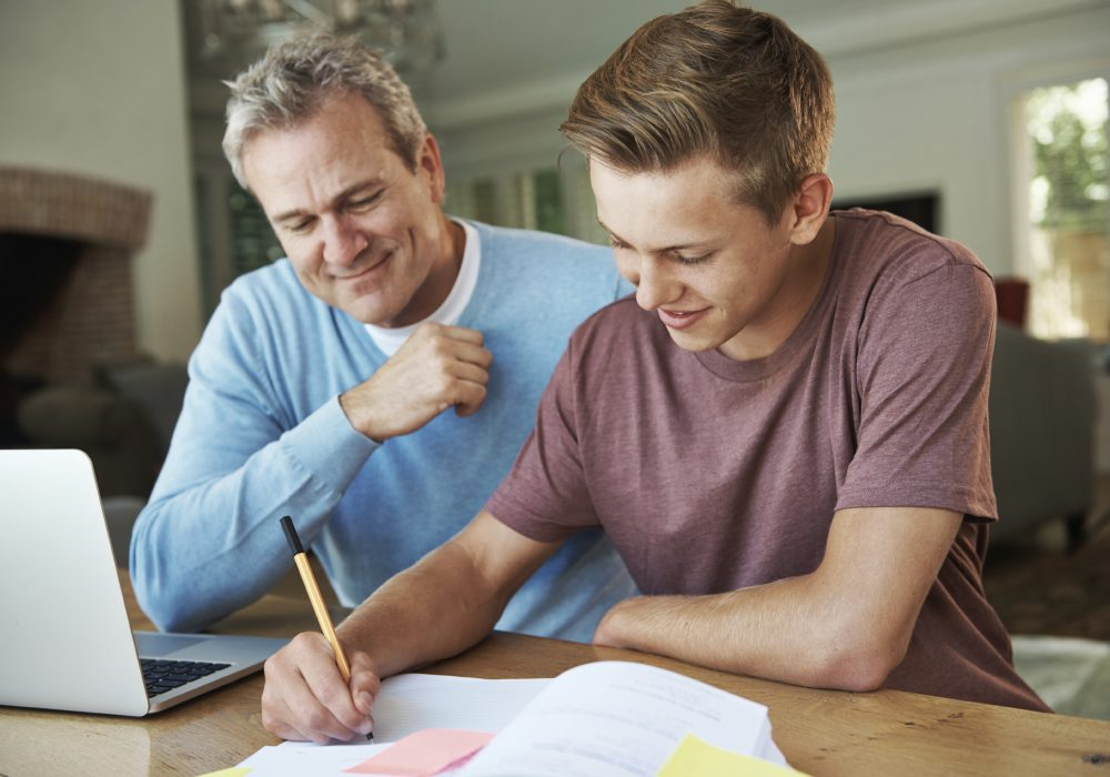 A father helping his teenage son with his homework
